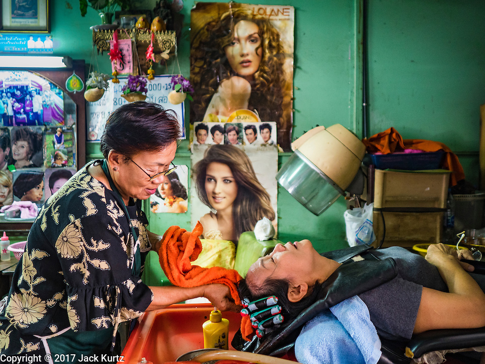 "06 FEBRUARY 2017 - BANGKOK, THAILAND: A customer (right) chats with her hairdresser in a shop in what used to be known as Kalabok Market under the Phra Khanong Bridge in the Phra Khanong district of Bangkok. Kalabok is the Thai word for hairdresser and the market was called Kalabok because there were many barbershops and hairdressers under the bridge. In 1985, the city changed the name of the market to ""Singha Market."" There are still about 10 small men's barbershops, most with just one barber, and four women's salons, most with one hairdresser,  under the bridge.      PHOTO BY JACK KURTZ"