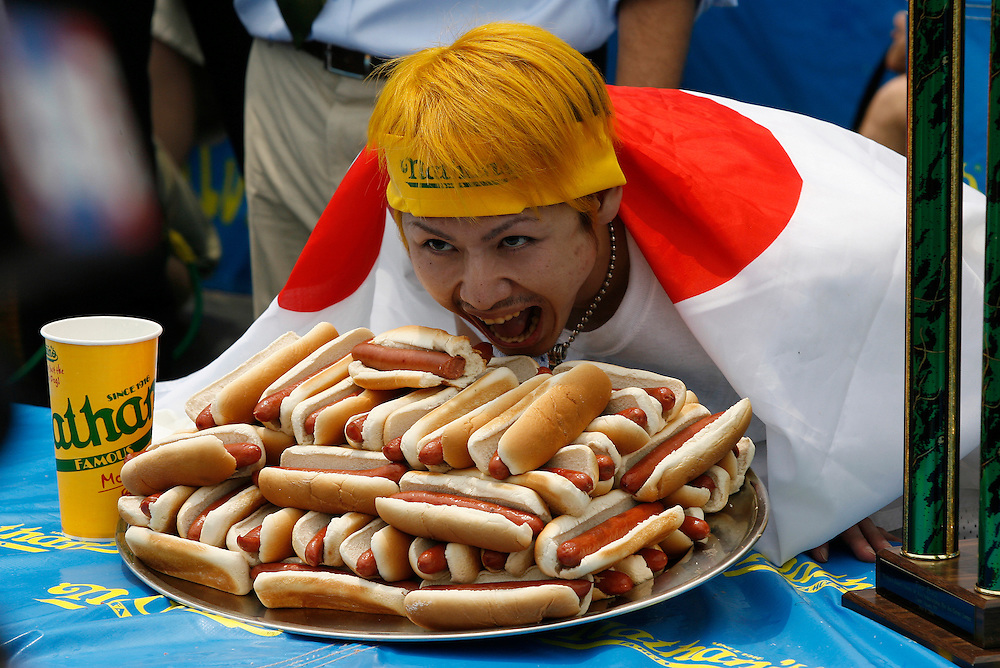 NEW YORK, NY-06 JUL04-- Draped in a Japanese flag, champion hot dog eater Takeru Kobayashi gloats over a tray representing the number of hot dogs he was able to consume in 12 minutes. (Extra) The Gazette/Liam Maloney