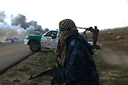 A Libyan rebel soldier walks nearby military vehicles of Qaddai's army burning that were hit by coalition forces on the road from Benghazi to Ajhtabiya Libya Mrch 20,2011. (Photo by Heidi Levine/Sipa Press~)
