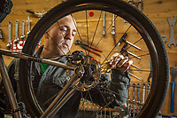 """Brad Suhr, owner of Calistoga Bike Shop, adjust his bike in the back-shop.  """"I started out banging nails for a living back east...later I worked part time for a bike shop and then managed a shop in Martha's Vineyard.  Nine years ago I purchased this shop with the intention of giving it five years.  We're still here and loving every minute.""""  calbikes@gmail.com"""