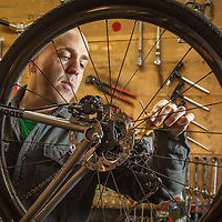 "Brad Suhr, owner of Calistoga Bike Shop, adjust his bike in the back-shop.  ""I started out banging nails for a living back east...later I worked part time for a bike shop and then managed a shop in Martha's Vineyard.  Nine years ago I purchased this shop with the intention of giving it five years.  We're still here and loving every minute.""  calbikes@gmail.com"
