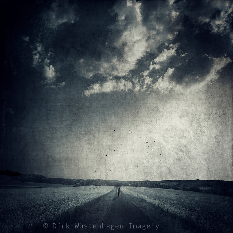 Man standing on a country road at sunset. Monochrome photograph with textures.