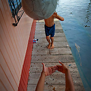 Two of the younger members of the Saldana Puscan family play on the small porch of the family's home. Dry real estate is hard to come by forcing children to spend much of their free time in the contaminated water. Image © Jonah Markowitz/Falcon Photo Agency