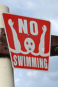 A No Swimming sign posted all around the pond at Kiwanis Park in Tempe, Arizona.
