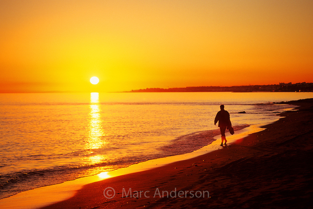 Silhouette of a man walking on a mediterranean beach at sunset, Costa Del Sol, Spain