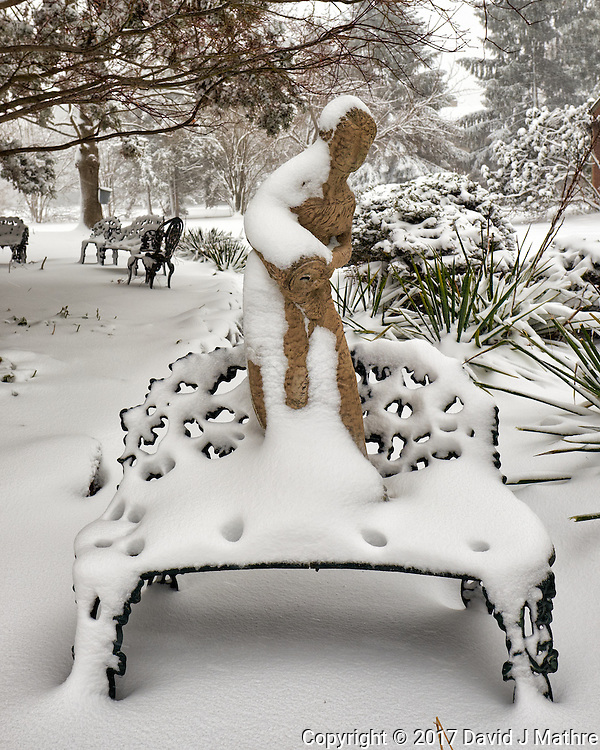 Birdbath statue standing on a bench covered with snow.  Image taken with a Fuji X-T1 camera and 16 mm f/1.4 lens (ISO 200, 16 mm, f/7, 1/125 sec).