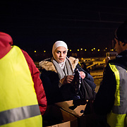2016 January–Tabanovce, Macedonia. A Syrian woman selects warm clothing, provided by NGOs, for her children after arriving from Gevgelija (the Macedonia-Greece border). Tabanovce is the transit stop before they cross the border into Serbia on their way into Western Europe in search of a peaceful life.  There is no train schedule-the trains leave Gevgelija when they fill up, therefore over the winter two to three trains a day have been arriving in Tabanovce at varying times of day and night.