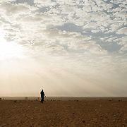 A man walks toward the savannah on the edge of the Mbera camp for Malian refugees in Mauritania on 3 March 2013.