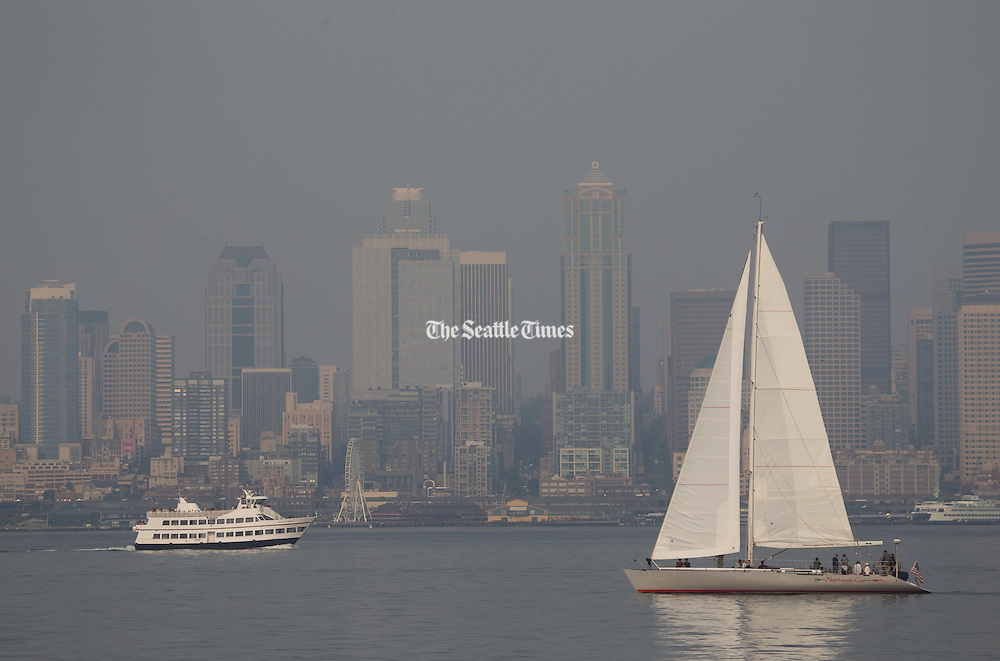 A sailboat and ferry pass by a hazy Seattle skyline, seen from the Alki Trail, as smoke, brought over by winds from the Eastern Washington wildfires, affects air quality and visibility in the area on Sunday, Aug. 23, 2015. <br />