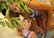 Mother and daughter at a live caterpillar show seeing a cecropia moth caterpillar for the first time.