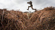 Rifleman Stuart Gray leaps an overgrown trench in a practice battlefield, where thousands of troops trained before embarking for the battlefields of Europe during World War One. The trench system was been discovered by chance on the Browndown Ministry of Defence site in Gosport, Hampshire, England. March 6, 2014. AFP PHOTO / CHRIS ISON.