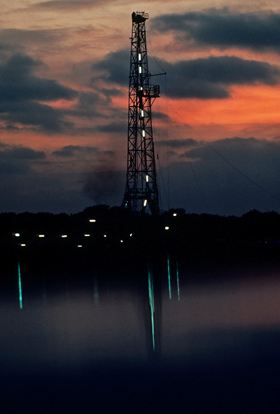 Stock photo of the silhouette of an on-shore rig through the fog