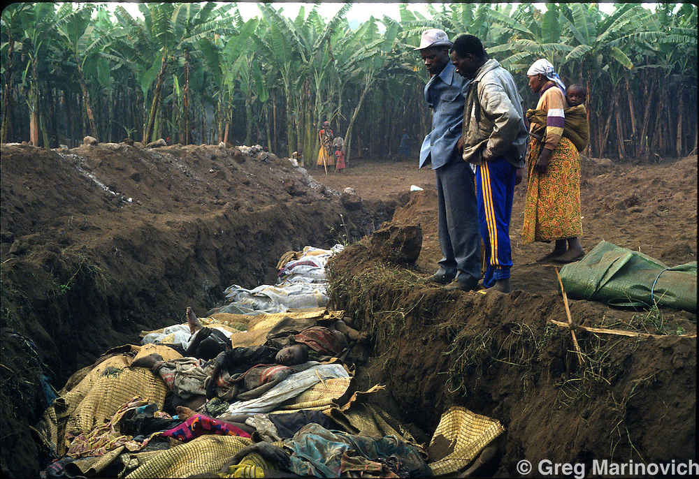 Goma, Zaire, Rwandan refugees look at bodies of a cholera epidemic being dumped in mass graves outside Goma, eastern Zaire. Millions of ethnic Hutus escaped the RPF takeover that followed and stopped the genocide of Rwandan Tutsis and Hutu moderates by extremist Hutus. 1994. Greg Marinovich