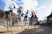 "Trinidad and Tobago ""MOKO JUMBIES: The Dancing Spirits of Trinidad"".(Students practice Limbo dancing and jumps in the yard. When two students lift one leg towards each other and hold onto it, another child can move below the legs Limbo style. Only experienced Moko Jumbies can perform this difficult dance.).A photo essay about a stilt walking school in Cocorite, Trinidad..Dragon Glen de Souza founded the Keylemanjahro School of Art & Culture in 1986. The main purpose of the school is to keep children off the streets and away from drugs..He first taught dances like the Calypso, African dance and the jig with his former partner Cathy Ann Samuel.  Searching for other activities to engage the children in, he rediscovered the art of stilt-walking, a tradition known in West Africa as the Moko Jumbies , protectors of the villages and participants in religious ceremonies. The art was brought to Trinidad by the slave trade and soon forgotten..Today Dragon's school has over 100 members from age 4 and up..His 2 year old son Mutawakkil is probably the youngest Moko Jumbie ever. The stilts are made by Dragon and his students and can be as high as 12-15 feet. The children show their artistic talents mostly at the annual Carnival, which today is unthinkable without the presence of the Moko Jumbies. A band can have up to 80 children on stilts and they have won many of the prestigious prizes and trophies that are awarded by the National Carnival Commission. Designers like  Peter Minshall , Brian Mac Farlane and Laura Anderson Barbata create dazzling costumes for the school which are admired by thousands of  spectators. Besides stilt-walking the children learn the limbo dance, drumming, fire blowing and how to ride  unicycles..The school is situated in Cocorite, a suburb of Port of Spain, the capital of Trinidad and Tobago..all images © Stefan Falke"