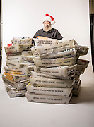 "Gabby Gaborik, Chief Elf who answers letters to ""Santa Claus"", in North Pole, Alaska. Seen here with some of the many thousands of letters he and other volunteers respond to each year.  Photographed in North Pole, Alaska  by Brian Smale, for People Magazine."