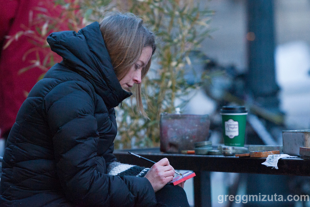 """Boise artist Rachel Teannalach paints her  365th tinyExpanse painting of her """"Year of Daily Paintings"""". The temperature was a chilly 15°F as she completed her final painting of the year outside of Dawson Taylor Coffee Roasters in downtown Boise, 8th and Bannock, December 1, 2015."""