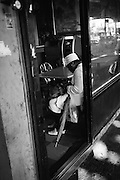 A woman wearing her Sunday best counts change to pay for dinner at a Chinese restaurant on Broadway in Bushwick, NY.