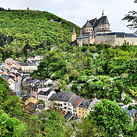 Vianden Castle and Row Houses in Vianden, Luxembourg <br /> A jewel of the small, landlocked country of Luxembourg in Western Europe is the Vianden Castle.  Built during the Middle Ages, it majestically stands on a promontory ridge above the Our River Valley and the row houses of the town below.  The Ch&acirc;teau de Vianden has all of the features of an iconic castle such as battlements, bastions and towers.  Inside is a wonderful historical museum that includes military exhibits such as suits of armor worn by knights.