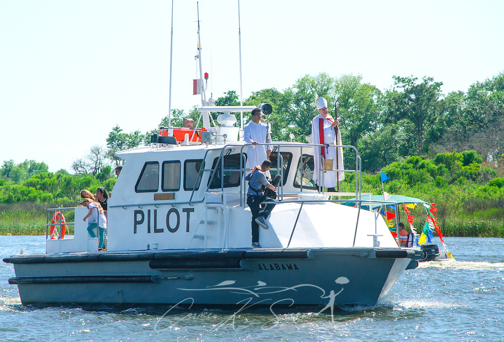 Catholic Archbishop Thomas J. Rodi, front, rides the pilot boat during the 66th annual Blessing of the Fleet in Bayou La Batre, Alabama, May 3, 2015. The first fleet blessing was held by St. Margaret's Catholic Church in 1949, carrying on a long European tradition of asking God's favor for a bountiful seafood harvest and protection from the perils of the sea. The highlight of the event is a blessing of the boats by the local Catholic archbishop and the tossing of a ceremonial wreath in memory of those who have lost their lives at sea. The event also includes a land parade and a parade of decorated boats that slowly cruise through the bayou. (Photo by Carmen K. Sisson/Cloudybright)