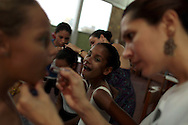 Girls fix their make up before their ballet class at the 'Ballet Santa Teresa' academy in Rio de Janeiro August 13, 2012. 'Ballet Santa Teresa', a non-governmental organization (NGO) gives children who live in areas with social risk, some suffering domestic violence, free ballet classes and other activities as a part of socio-cultural integration project. Photo by: Pilar Olivares