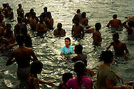 A modern girl baths among a group of men. Contemporary and traditional India get together in the water.