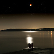 People watch the full moon as it starts to come out of total eclipse on Sequim Bay, WA. It was a perigee moon (when the moon is closest to Earth) and a total lunar eclipse which coincided for a few hours, resulting in a total eclipse of the largest full moon of the year. Although these astronomical events can happen separately several times a year, this combination has only happened five times since 1900, with the last coming in 1982. If you missed this one, you won't get another chance until 2033!