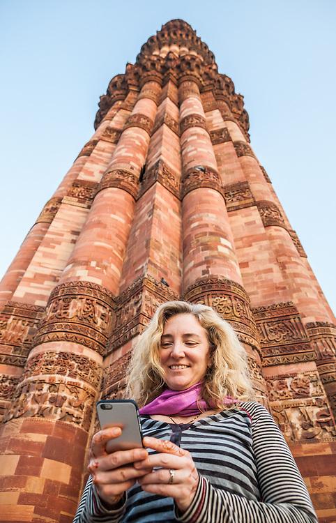 Woman using an iPhone below Qutb Minar in Delhi, India.