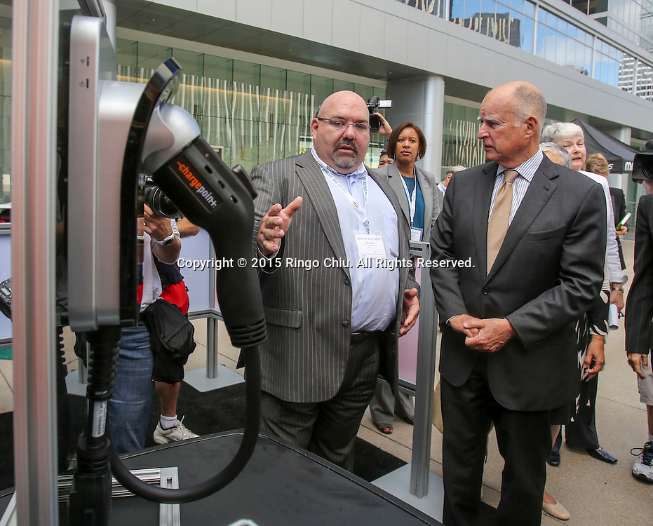 California Gov. Jerry Brown, right listens as Mike DiNucci, left,  of ChargePoint, introduces their charging station in Drive the Dream 2015 event at Creative Artists Agency in Los Angeles October 15, 2015.  (Photo by Ringo Chiu/PHOTOFORMULA.com)