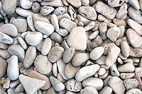 Små runde steiner i strandkanten, small rounded stones at the beach