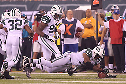 Aug 26, 2012; East Rutherford, NJ, USA; New York Jets linebacker Calvin Pace (97) and New York Jets defensive end Quinton Coples (98) try to recover a fumble by Carolina Panthers running back DeAngelo Williams (34) during the first half at MetLife Stadium.