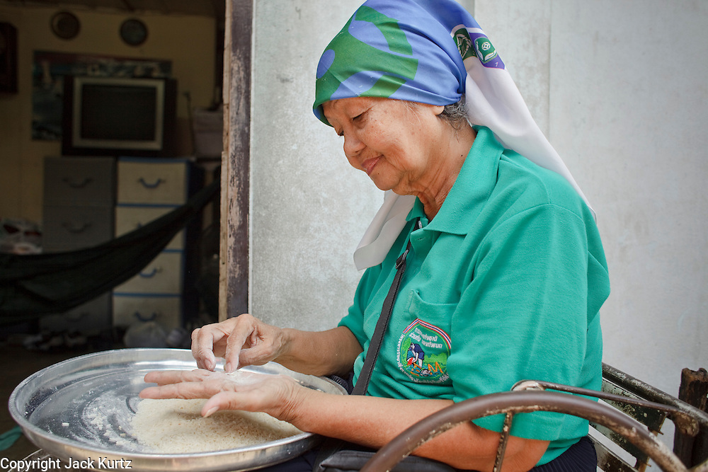 """Mar 23, 2009 -- BANGKOK, THAILAND: A Moslem woman sorts rice in front of her home in Ban Krua. The Ban Krua neighborhood of Bangkok is the oldest Muslim community in Bangkok. Ban Krua was originally settled by Cham Muslims from Cambodia and Vietnam who fought on the side of the Thai King Rama I. They were given a royal grant of land east of what was then the Thai capitol at the end of the 18th century in return for their military service. The Cham Muslims were originally weavers and what is known as """"Thai Silk"""" was developed by the people in Ban Krua. Several families in the neighborhood still weave in their homes.     Photo by Jack Kurtz"""