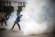 A protester throws tear gas back at the riot police on the 26th of June 2011, the same day the government of Greece accepted the tough austerity measures demanded by the EU and IMF, Athens, Greece. Image © Angelos Giotopoulos/Falcon Photo Agency