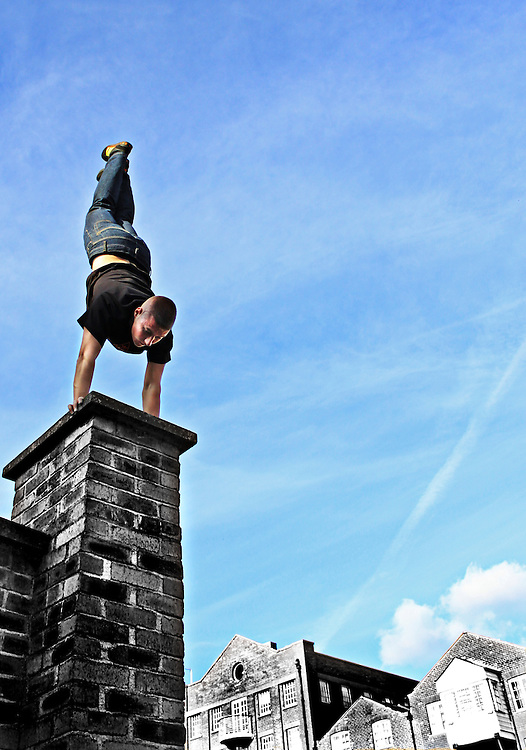 Cheerleader/Tricker/Freerunner Jack Lowry doing a Handstand on a wall next to the canal running past The Calls in Leeds city centre