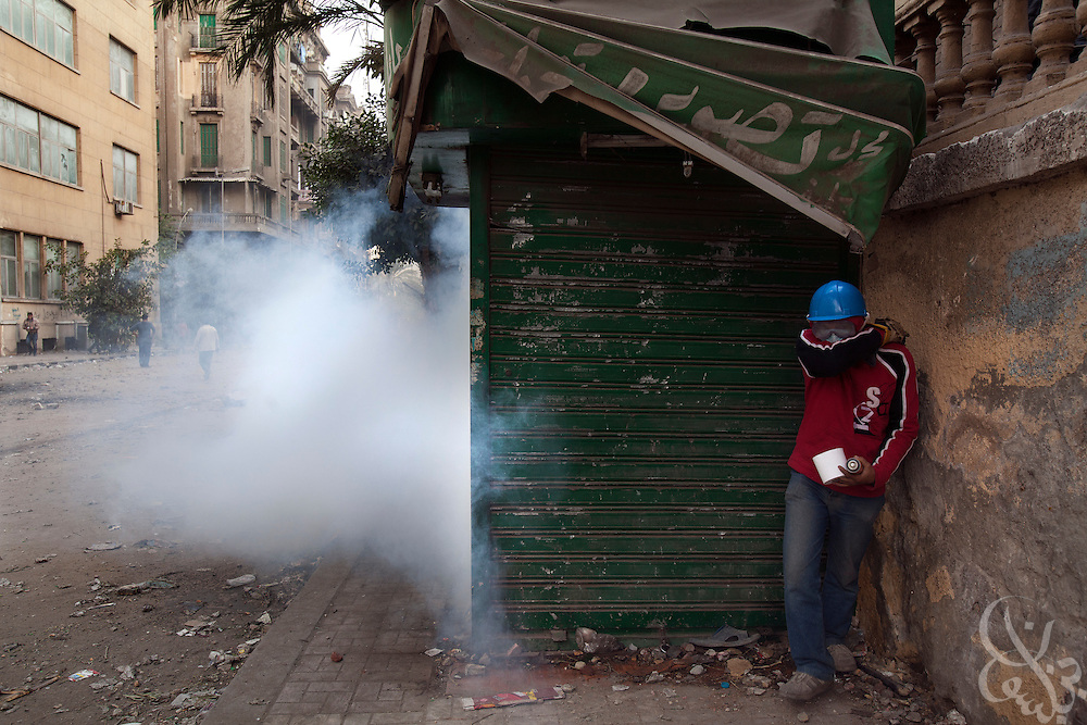 An Egyptian protestor tries to take cover from tear gas fired by nearby security forces during street battles November 21, 2011 near Tahrir square  in central Cairo, Egypt. Thousands of protestors demanding the military cede power to a civilian government authority clashed with Egyptian security forces for a third straight day in Cairo, with hundreds injured and at least 24 protestors killed.  (Photo by Scott Nelson)