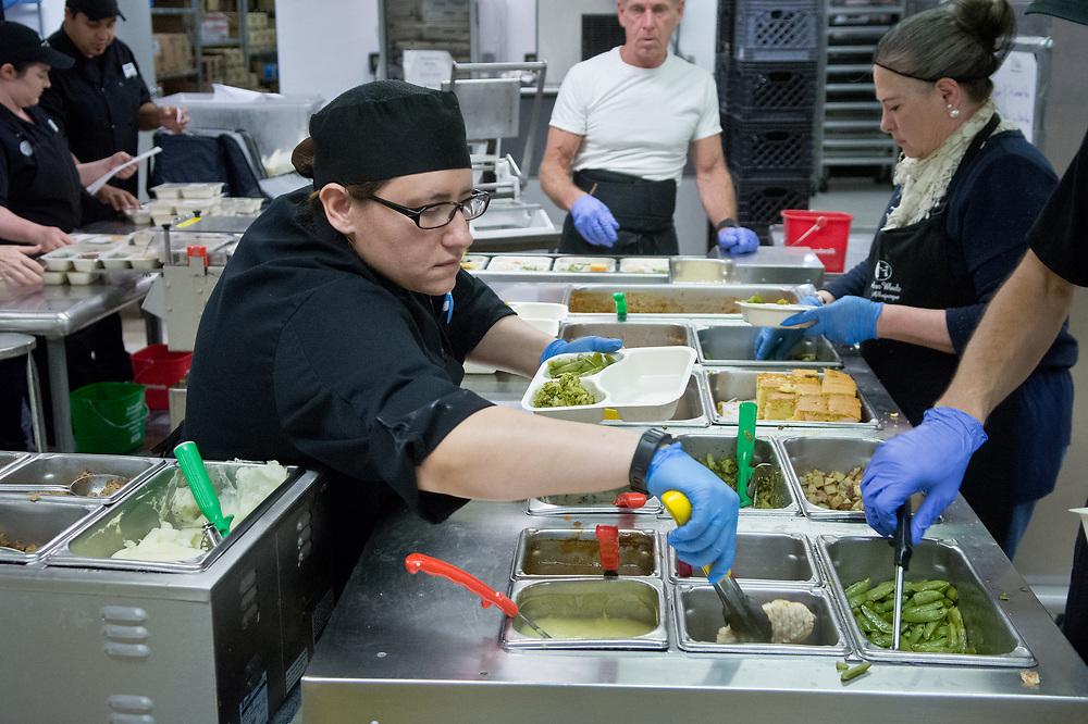 mkb032417/metro/Marla Brose --  Soozi Becerra, center, fills trays with food at the Meals on Wheels kitchen in Albuquerque, N.M., Friday, March 24, 2017. Meals on Wheels delivers about 550 meals a day. (Marla Brose/Albuquerque Journal)
