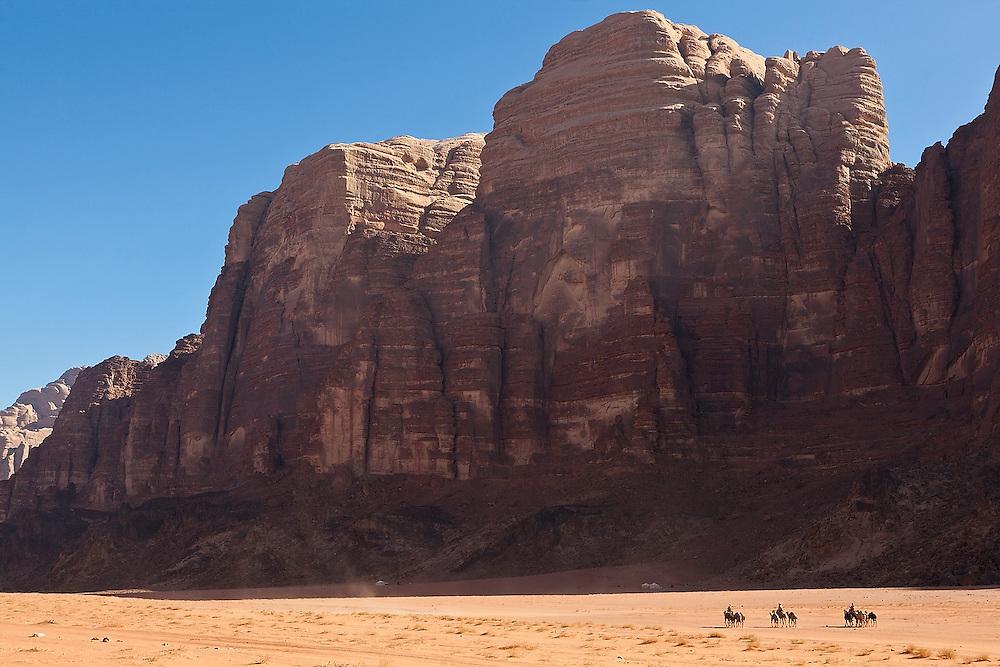 Bedouin men ride racing camels through the desert in Wadi Rum, Jordan.