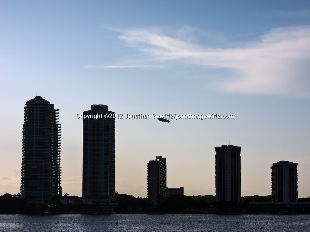 A Goodyear blimp climbs in the late-afternoon sky behind the silhouettes of condominium buildings on Miami's Brickell Avenue. WATERMARKS WILL NOT APPEAR ON PRINTS OR LICENSED IMAGES.