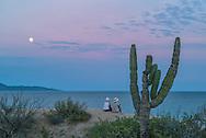 Mexico, Baja California sur, Baja, La Ventana, Sea of Cortez, two women watchhing moonrise at Palapa beach, MR  0350, 0450