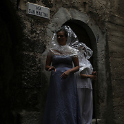 Women wearing costumes as a form of art installation stand in a street of the mostly abandoned old centre of the town of Catsel Vecchio in the province of L'Aquila in Abruzzo.