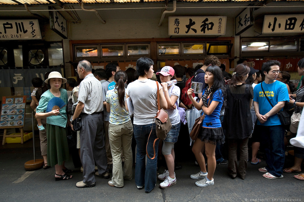 People queueing around 9 am outside Daiwa, a famous sushi restaurant in Tsukiji market. The restaurant opens every day at 5:30 in the morning and it's clients start queueing from 5 am to enter. At the time passes the queue grows longer and  people have to wait for almost hours before they get in.  Tsukiji fish market  is the biggest wholesale fish and seafood market in the world and also one of the largest wholesale food markets of any kind. The market is located in Tsukiji in central Tokyo, and is a major attraction for foreign visitors.