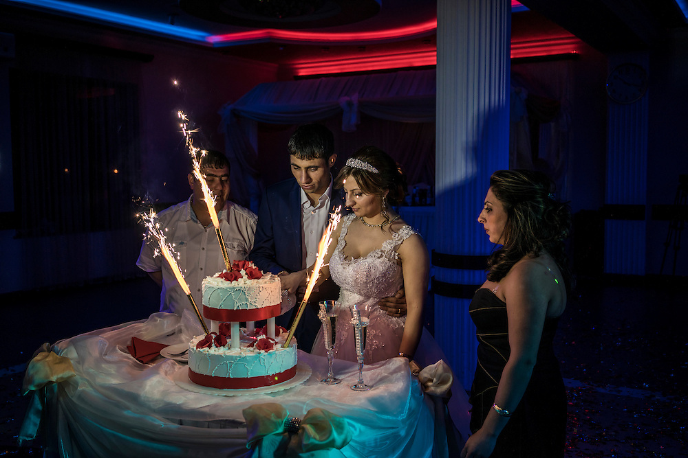 STEPANAKERT, NAGORNO-KARABAKH - APRIL 18: Groom Davit Simonyan, 24, and bride Shogher Hovsepyan, 25, prepare to cut the cake at their wedding reception on April 18, 2015 in Stepanakert, Nagorno-Karabakh. Since signing a ceasefire in a war with Azerbaijan in 1994, Nagorno-Karabakh, officially part of Azerbaijan, has functioned as a self-declared independent republic and de facto part of Armenia, with hostilities along the line of contact between Nagorno-Karabakh and Azerbaijan occasionally flaring up and causing casualties. (Photo by Brendan Hoffman/Getty Images) *** Local Caption *** Davit Simonyan;Shogher Hovsepyan