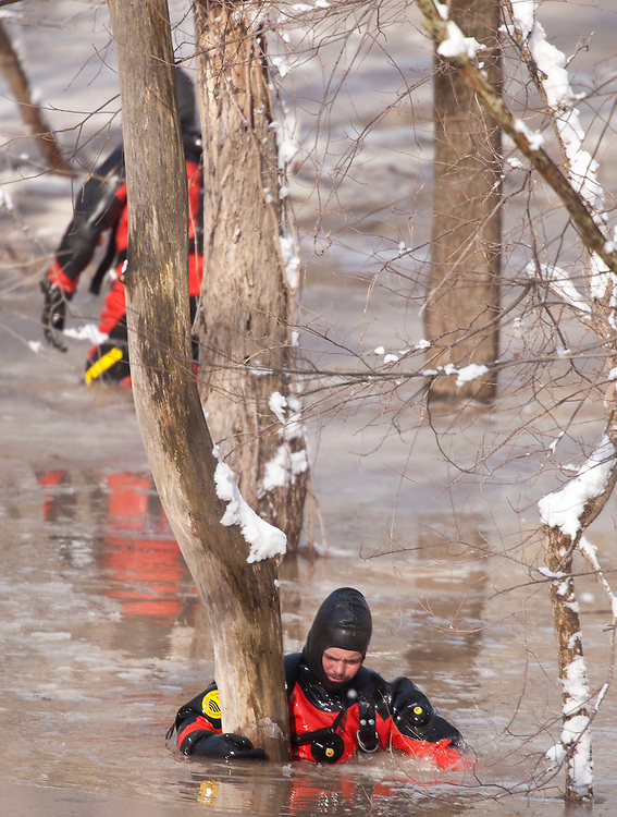 Ontario Provincial Police divers search Sunday, March 6, 2011, for a missing 10 year old girl who fell through the ice Saturday in a creek behind her home near Melborne Ontario.<br /> THE CANADIAN PRESS/ Geoff Robins
