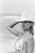 woman in a bikini top and cowboy hat at the beach
