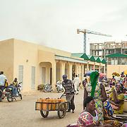LÉGENDE: Vue d'ensemble du nouveau batîment administratif du marché construit par la BAD. On peut voir aussi quelques vendeuses à droite de l'image. LIEU: Marché de Chagoua, N'Djaména, Tchad. PERSONNE(S): Un homme (au centre) pousse un chariot. A droite, des vendeuses assisent devant leur stands.