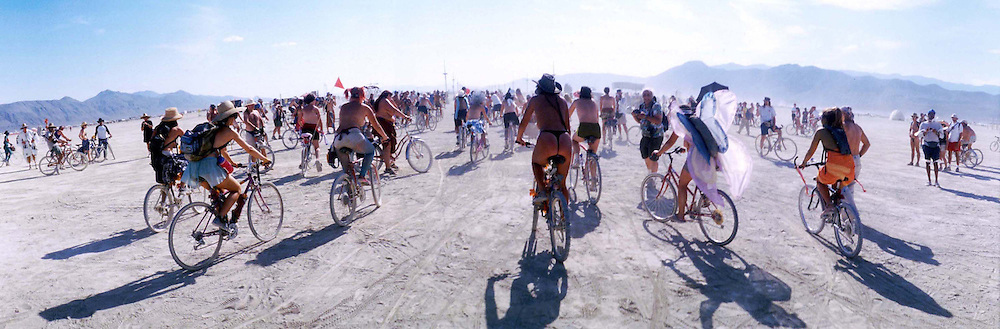 """Bikers begin a group bike tour around the desert during the16th annual Burning Man festival, August 29, 2001 in the Black Rock Desert near Gerlach, Nevada.An estimated record 29,000 people camped out on a remote desert playa, or dry lake, for the week-long counter-cultural celebration of art and """"radical self-expression."""" This year's theme was thethe stages of man."""