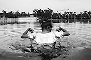 Due to adequate public lavatories a street prostitute has no other choice to have her bath in a contaminated lake in the park.