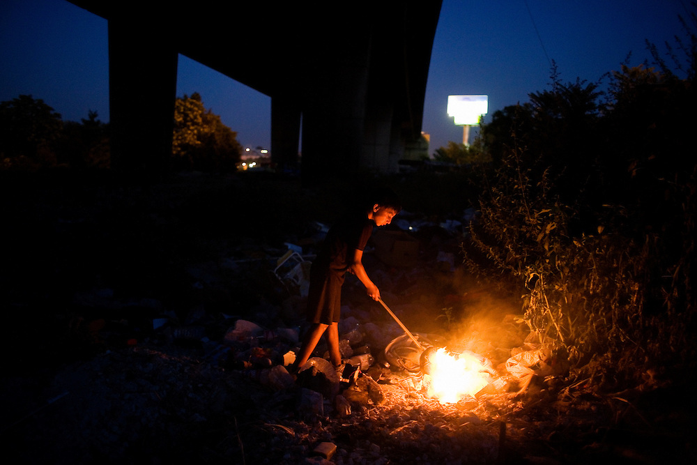 A boy plays with a garbage fire underneath the Gazela Bridge in the Nova Gazela settlement.