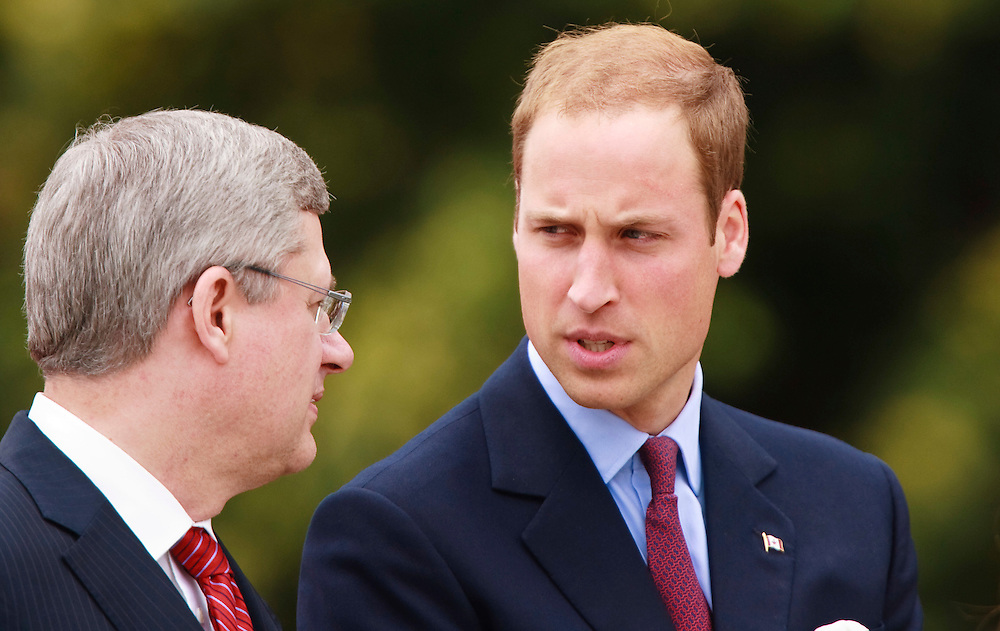 Prince William speaks with Canadian Prime Minister Stephen Harper during a ceremony at the National War Memorial in Ottawa, Canada,  June 30, 2011, the first stop on their nine-day tour of Canada, kicking off their first official foreign trip as husband and wife.<br /> AFP PHOTO/GEOFF ROBINS