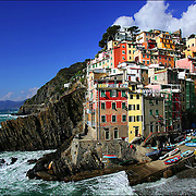 SHOT 3/1/2006 - The town of Riomaggiore in Cinque Terre, Italy. Riomaggiore (Rimas&ugrave;u in the local language) is a village and a commune in the province of La Spezia, situated in a small valley in the Liguria region of Italy. It is the first of the Cinque Terre one meets coming from La Spezia. Riomaggiore, the first city of the Cinque Terre.<br /> The village, dating from the early thirteenth century, is known for its historic character and its wine, produced by the town's vineyards. Riomaggiore is in the Riviera di Levante region and has shoreline on the Mediterranean's Gulf of Genoa, with a small beach and a wharf framed by tower houses. Riomaggiore has one or two roads where people go and hang out, but most of the life at night can be found at the Bar Centrale.<br /> The Via dell'Amore is a path connecting Riomaggiore to its frazione Manarola, also part of the Cinque Terre.<br /> Riomaggiore is the most southern village of the five Cinque Terre, all connected by trail. The water and mountainside have been declared national parks.<br /> (MARC PISCOTTY/ &copy; 2006)