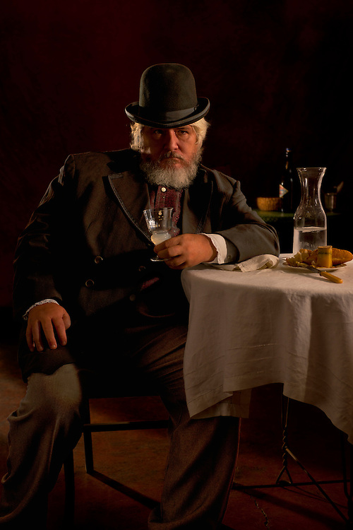 Portrait of a French man in the days before absinthe was prohibited. He's enjoying his absinthe and cheese after a long work day.